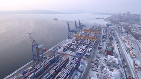 Russia Far East Vladivostok commercial port terminal. Transport logistics center. Winter cold day sea. Snow steel containers. Unique aerial drone 4k cinematic stock video footage