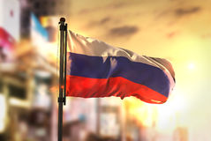 Russia Flag Against City Blurred Background At Sunrise Backlight Stock Photos