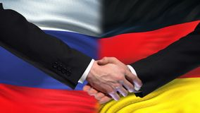 Russia and Germany handshake, international friendship summit, flag background. Stock footage stock video
