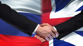 Russia and Great Britain handshake, international friendship, flag background. Stock footage stock video