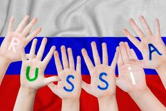 Russia inscription on the children`s hands against the background of a waving flag of the Russian Federation.  stock images