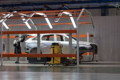 Russia, Izhevsk - December 15, 2018: LADA Automobile Plant Izhevsk. The female worker set a detail on the new car. Russia, Izhevsk - December 15, 2018: LADA royalty free stock photos