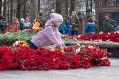 Russia, Izhevsk - May 9, 2018: The girl is laying flowers at the memorial to the fallen soldiers of World War II. Red carnation flowers on a memorial marble royalty free stock photography