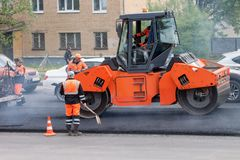 Russia, Izhevsk - May 30, 2018: Road building. Repair and replacement of old asphalt pavement. Men at work stock images