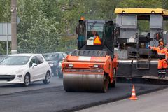 Russia, Izhevsk - May 30, 2018: Road work. Repair and replacement of old asphalt pavement. Asphalt layover. Using a special road roller stock photography