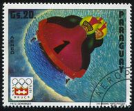 Winter Olympics in Innsbruck. RUSSIA KALININGRAD, 19 APRIL 2017: stamp printed by Paraguay, shows 4 man bobsled at Winter Olympics in Innsbruck, circa 1975 Royalty Free Stock Photos