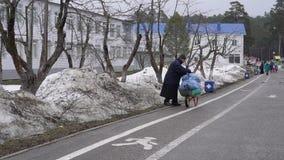 Russia, Kazan - April 7, 2019: The Raifa Bogoroditsky Monastery. An elderly churchman cleans up litter on an overcast day. stock video footage