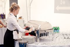 Free Russia Kemerovo 2019-07-27 Blonde Waiter Girl In Uniform, White Shirt, Black Apron At Catering Party Prepares For Banquet, Make Stock Images - 157548044