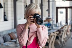 Russia Kemerovo 2019-03-10 girl photographer taking pictures on professional camera Canon 5D Mark IV in restaurant. Concept stock photos