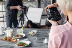 Russia Kemerovo 2019-03-10 girl photographer taking pictures on professional camera Canon 5D Mark IV and various dishes, salads on stock photos