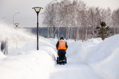 Russia Kemerovo 2019-02-22 Janitor in uniform orange vest cleans pavement, pedestrian walkway from snow with snow machine on. Russia Kemerovo 2019-02-22 Janitor royalty free stock image