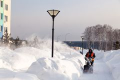 Russia Kemerovo 2019-02-22 Janitor in uniform orange vest cleans pavement, pedestrian walkway from snow with snow machine on. Russia Kemerovo 2019-02-22 Janitor royalty free stock images