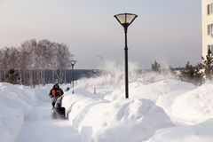 Russia Kemerovo 2019-02-22 Janitor in uniform orange vest cleans pavement, pedestrian walkway from snow with snow machine on. Russia Kemerovo 2019-02-22 Janitor stock photo