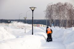 Russia Kemerovo 2019-02-22 Janitor in uniform orange vest cleans pavement, pedestrian walkway from snow with snow machine on. Russia Kemerovo 2019-02-22 Janitor stock images