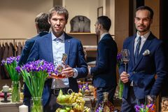 Russia Kemerovo 16-11-2018 two men hold bottle and glass on degustation Remy Martin XO luxury cognac, beautiful buffet table with. Flowers and snacks. Concept royalty free stock images