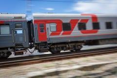 Passenger wagon of train with the inscription RZHD in motion. Motion blur. RUSSIA, KRASNODAR KRAI, GIZELE-DERE VILLAGE, August 10, 2018: Passenger wagon of train royalty free stock image