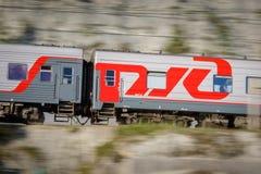 Passenger wagon of train with the inscription RZHD in motion. Motion blur. RUSSIA, KRASNODAR KRAI, GIZELE-DERE VILLAGE, August 10, 2018: Passenger wagon of train royalty free stock photography