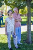 Elderly man and woman standing on the lawn and looking into the distance stock photo
