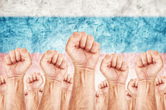 Russia Labour movement, workers union strike. Concept with male fists raised in the air fighting for their rights, Russian national flag in out of focus Stock Photo