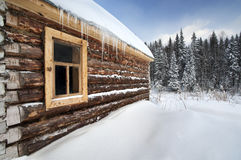 Russia log house in winter, with fir trees. In background at Urals, Russia Royalty Free Stock Photo