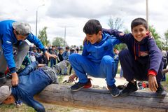 Russia, Magnitogorsk, - June, 15, 2019. Children of migrants play on a log during Sabantuy - the national holiday of the plow. Outdoor city park stock photo