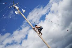 Russia, Magnitogorsk, - June, 15, 2019. A man climbs onto a tall pole for gifts during the traditional game of a Muslim holiday -. Sabantuy. Outdoor city park royalty free stock images