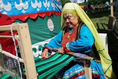 Russia, Magnitogorsk, - June, 15, 2019. An older woman works at an artisan loom. The participant of the street parade during. Sabantuy is a folk plow festival royalty free stock images
