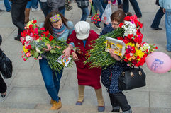 RUSSIA - MAY 09: Female World War II veteran with a bouquet of f. Russia, St. Petersburg - MAY 9: day of victory, memory of heroes. The memory of soldiers in Stock Photo