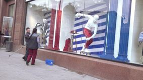 Washing the glass of the sports shop. RUSSIA, MOSCOW - April 10, 2018: Washing the glass of the sports shop. Charitable festival Easter gift in Moscow in April stock video