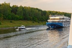 Russia, Moscow August 2018: small high-speed boat and motor ship floating on the river channel of Moscow.  royalty free stock image