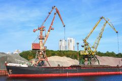 Russia, Moscow August 2018: Unloading of the barge with crushed stone port. Cranes in the port stock photos