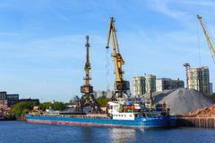 Russia, Moscow August 2018: Unloading of the barge with crushed stone port cranes in the port.  stock photo