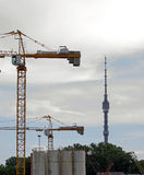 Russia, Moscow - construction cranes and Ostankino TV Tower. On a background cloudy sky royalty free stock photography