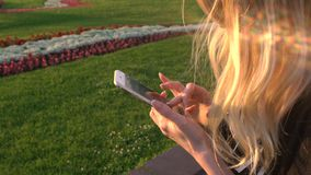 RUSSIA, MOSCOW - JULY 23, 2016: The beautiful blonde with iPhones leafing through photos in the park VDNKH stock video footage