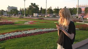 RUSSIA, MOSCOW - JULY 23, 2016: The beautiful blonde with iPhones leafing through photos in the park VDNKH stock video