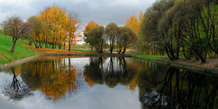 Russia. Moscow. Kolomenskoye museum-reserve. Mirror surface of pond surrounded by colorful trees. Fall postcard stock photos