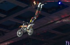 Risk trick on a motorcycle. RUSSIA, MOSCOW-MARCH 2: Unidentified sportsman doing tricks on his bike at the VI festival of extreme sports in the Olympic Sports Royalty Free Stock Image
