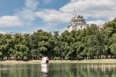 Russia, Moscow. Patriarch`s Ponds. View of Patriarch Ponds, park and luxury apartment reflected in water. Affluent residential area in Moscow stock photos