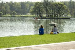 01-05-2018, Russia, Moscow, Tsaritsyno park manor, May holidays in the park, women are resting on the lake on a green lawn. A girl royalty free stock images