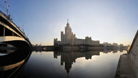 Russia. Moscow. View on classical Stalin's tower. Building on Kotelnicheskaya quay across Moskva river at a sunrise and Ust'inskiy bridge. Panorama royalty free stock photography
