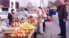 Russia, Novosibirsk, 2 april 2015. People choosing and buying fruit and vegetables outdoors in the bio market. 1920x1080 stock video
