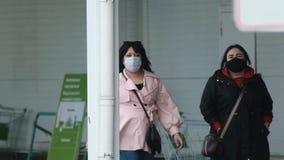 Masked women buyer walk in store street corona virus. People protected covid-19.
