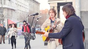 Russia, Novosibirsk, April 2019: Street musicians play guitars and sing songs for passersby. Slow motion.  stock video