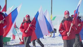 Russia, Novosibirsk, 2016: Athletes in winter clothes carry the Russian flag. Column athlete carries the flag of Russia. Opening of sports competitions. Winter stock footage
