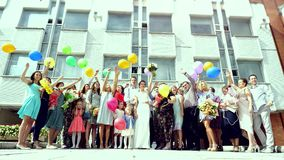 Russia, Novosibirsk, 11 august 2017. Happy wedding guests with the bride and groom jumping with balloons after stock footage