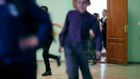 Russia, Novosibirsk, 2015: The bell rings, kids run from the school office. Russia, Novosibirsk, 2015: Group of elementary school kids running in a school stock footage