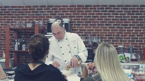 Russia Novosibirsk 2016. Chef explaining a to make a dish to group. Russia Novosibirsk 2016. The chef in the kitchen. Chef cook teaches a group of people. Master stock video
