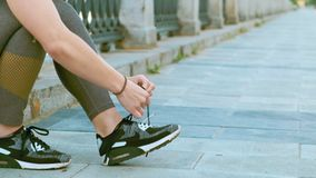 RUSSIA, NOVOSIBIRSK - 06-19-2019: Girl runner tying laces for jogging her shoes on promenade near the river. RUSSIA, NOVOSIBIRSK - 06-19-2019: Close-up foot stock video