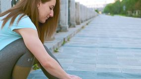 RUSSIA, NOVOSIBIRSK - 06-19-2019: Girl runner tying laces for jogging her shoes on promenade near the river. RUSSIA, NOVOSIBIRSK - 06-19-2019: Close-up Girl stock video footage