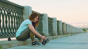 Russia, Novosibirsk - 06-19-2019: Girl runner tying laces for jogging her shoes on promenade near the river. Sport lifestyle stock footage